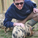 Stroking a piglet at Laineys Farm, a day care centre for adults with learning difficulties